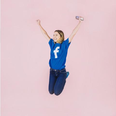 mujer saltando sosteniendo un teléfono móvil